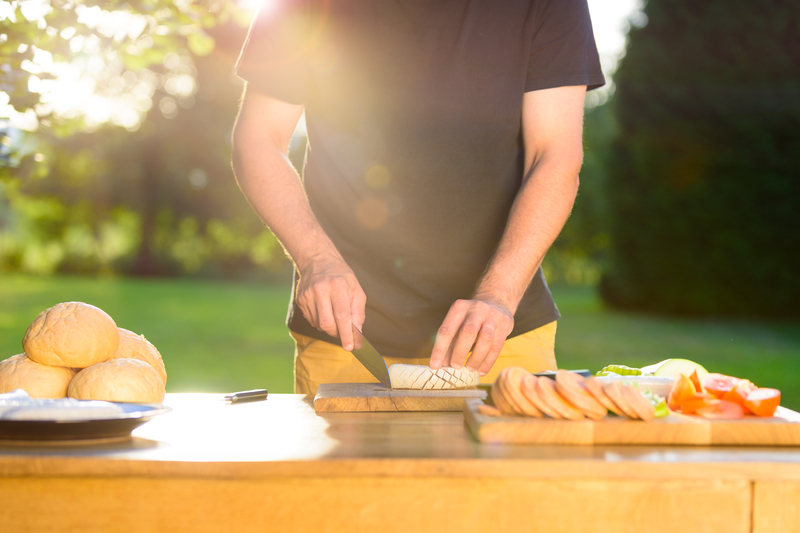 Man cutting food for summer garden party
