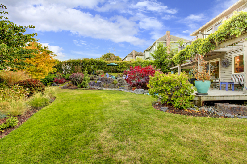 Large fenced backyards with fall landscape and view of the deck.