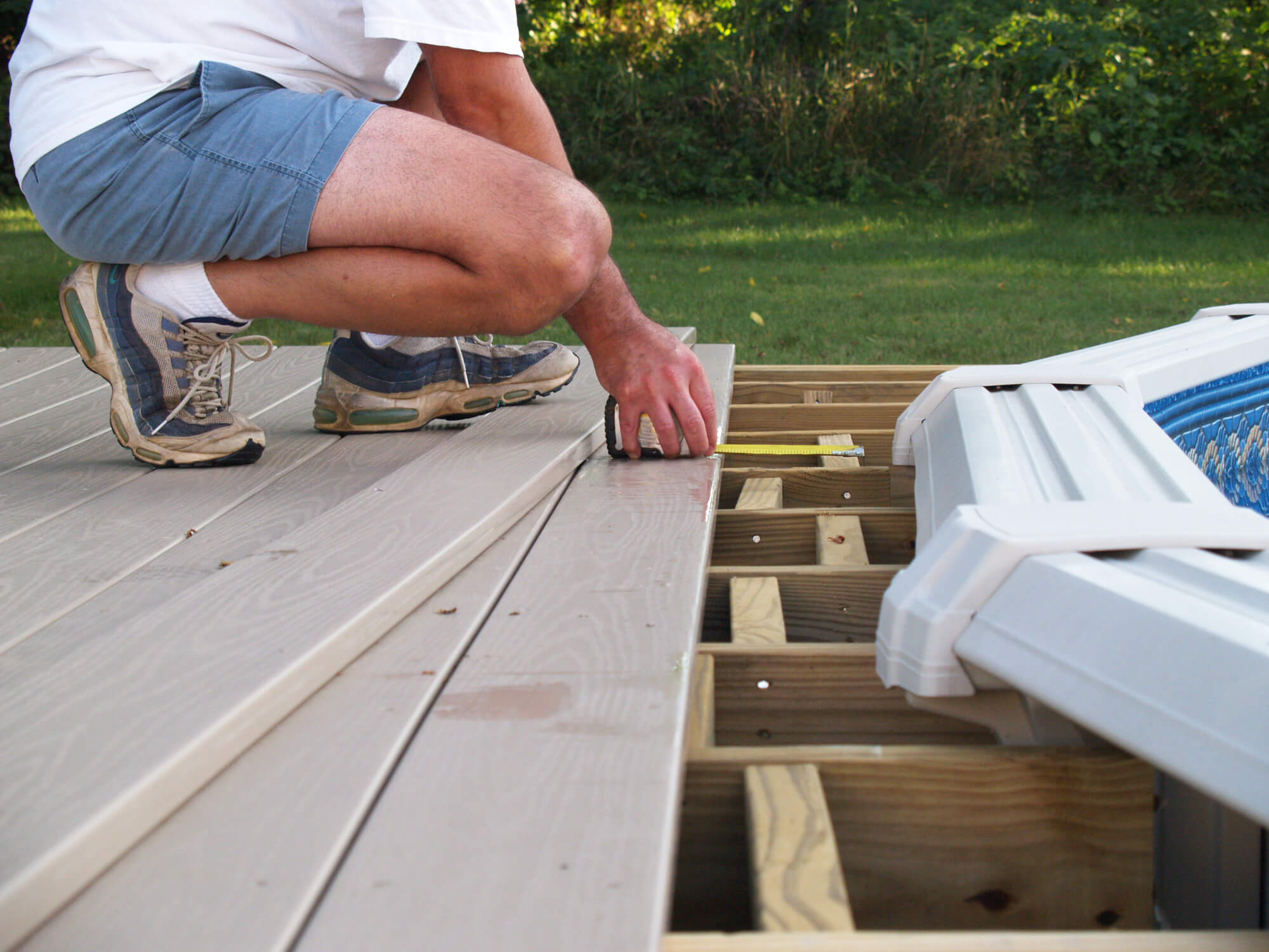 A landscaper is doing a decking in the garden.